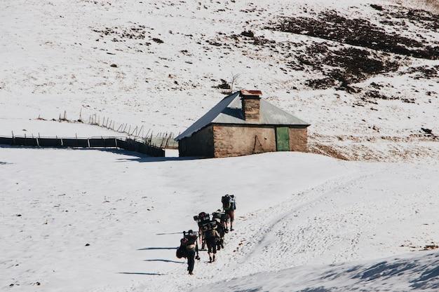 Pessoas com mochilas escalando a montanha no inverno