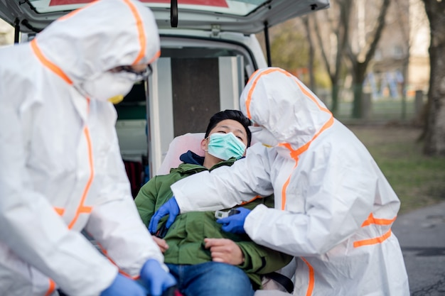Pessoas com roupas de proteção e respiradores, ajudando o homem ao ar livre, o conceito de coronavírus.