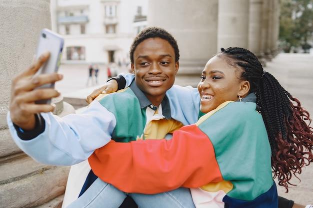 Pessoas com roupas idênticas. casal africano na cidade de outono. pessoas sentadas e usam o telefone.