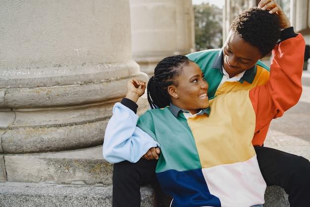 Pessoas com roupas idênticas. casal africano na cidade de outono. pessoas sentadas na rua.