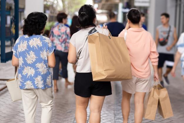 Pessoas com sacolas de papel na rua