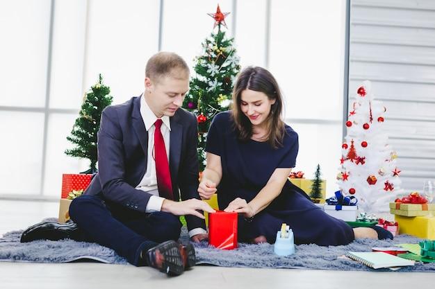 Pessoas com um presente presente na árvore de natal da festa de natal e réveillon