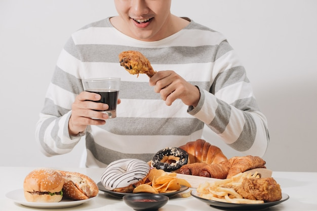 Pessoas comendo fast food com a mão segurando um refrigerante gaseificado de frango frito