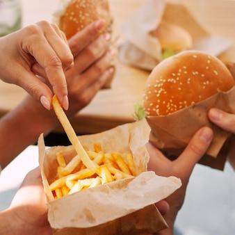 Pessoas comendo fast food com batatas fritas e hambúrguer