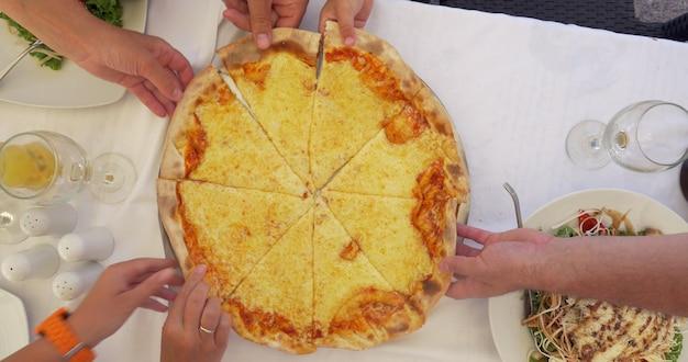 Pessoas comendo fatias de pizza de queijo servidas em um café