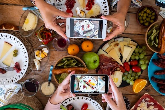 Pessoas comendo juntas tirando fotos de comida com o smartphone para compartilhar nas redes sociais