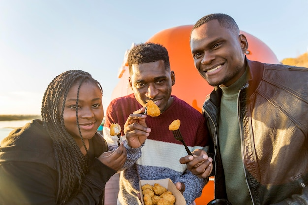 Pessoas comendo nuggets de frango em embalagens de comida para viagem