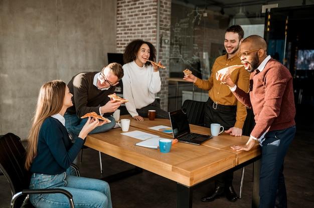 Pessoas comendo pizza durante o intervalo da reunião do escritório