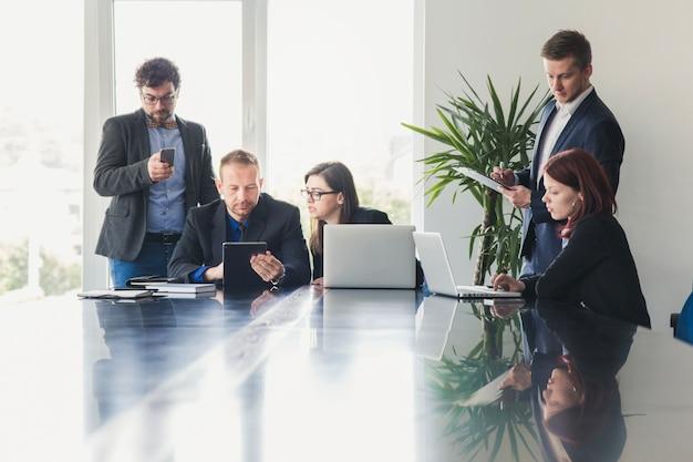 Pessoas comuns com gadgets na reunião