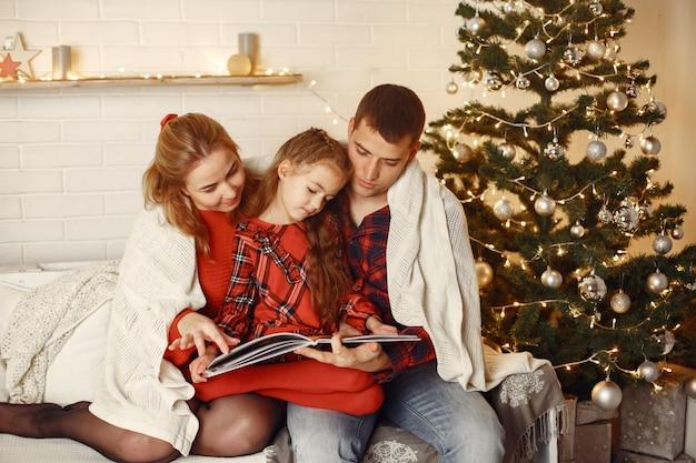 Pessoas consertando para o natal. pais brincando com a filha.