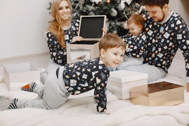 Pessoas consertando para o natal. pessoas brincando com uma criança. família está descansando em uma sala festiva.
