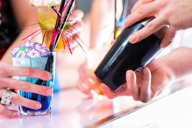 Pessoas, copos de cocktails e barman