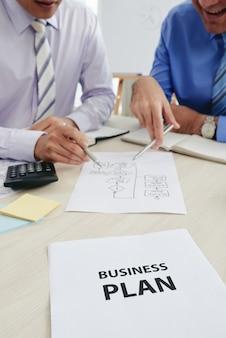 Pessoas cortadas em trajes formais discutindo o plano de negócios