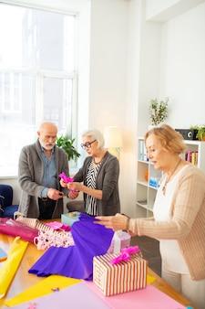 Pessoas criativas de cabelos grisalhos em pé à mesa enquanto empacotam o presente juntos