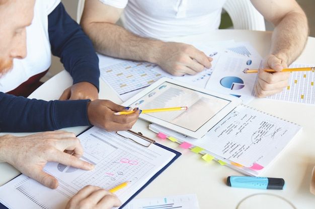 Pessoas criativas de diversas etnias trabalhando juntas no plano de negócios, analisando a taxa de crescimento, o valor dos bens e serviços, estudando o mercado, contando as perdas, usando o touch pad pc e fazendo anotações