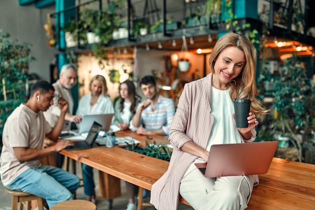 Pessoas criativas multirraciais em um escritório moderno. grupo de jovens empresários e chefe sênior estão trabalhando juntos com laptop, tablet, smartphone, caderno, gráficos. equipe de sucesso em coworking