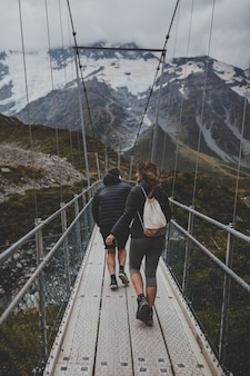 Pessoas cruzando uma ponte em mount cook, na nova zelândia