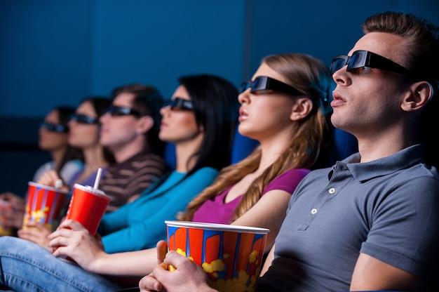 Pessoas curtindo filme tridimensional. jovens em óculos tridimensionais assistindo filme enquanto estão sentados no cinema