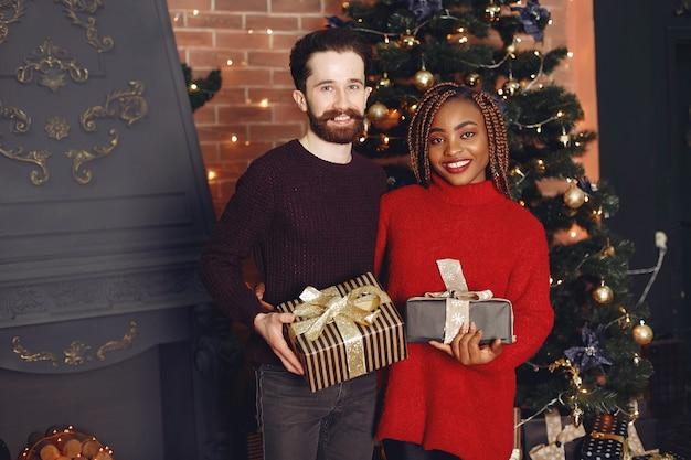 Pessoas da internet em casa. casal em uma decoração de natal. mulher africana e homem caucasiano.