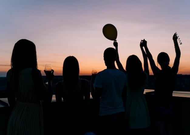 Pessoas dançando na festa no terraço no amanhecer