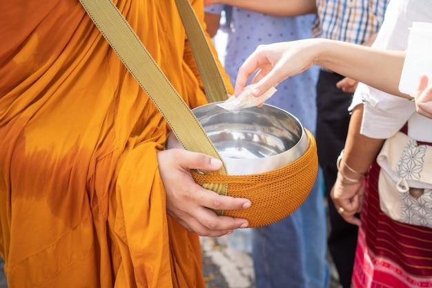 Pessoas dando esmolas a um monge budista