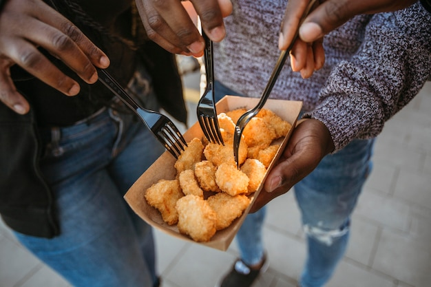 Pessoas de alto ângulo comendo nuggets em embalagens de comida para viagem
