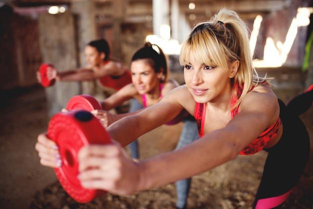 Pessoas de aptidão atraente malhando pernas de treinamento fazendo agachamentos.
