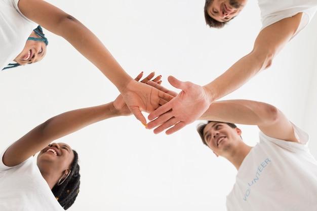 Pessoas de baixo para cima colocando as mãos umas nas outras