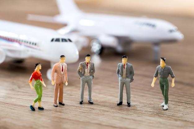 Pessoas de brinquedo pequeno estão de frente para o avião