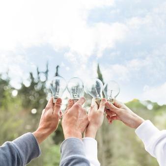 Pessoas de conceito segurando bulbos de vidro no ar