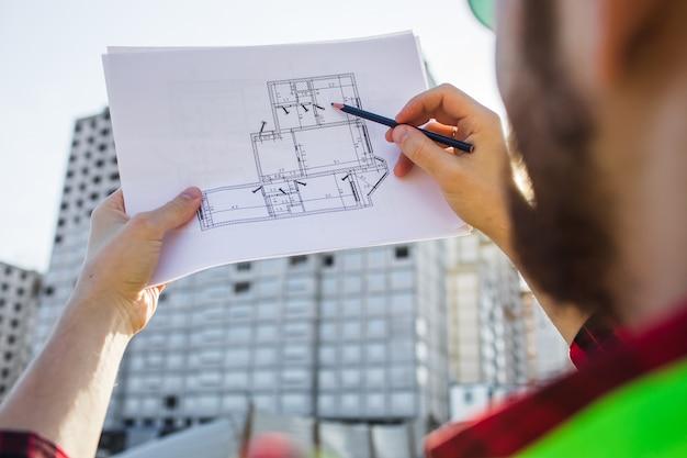 Pessoas de consultoria de engenharia no canteiro de obras com planta na mão. inspetor de construção