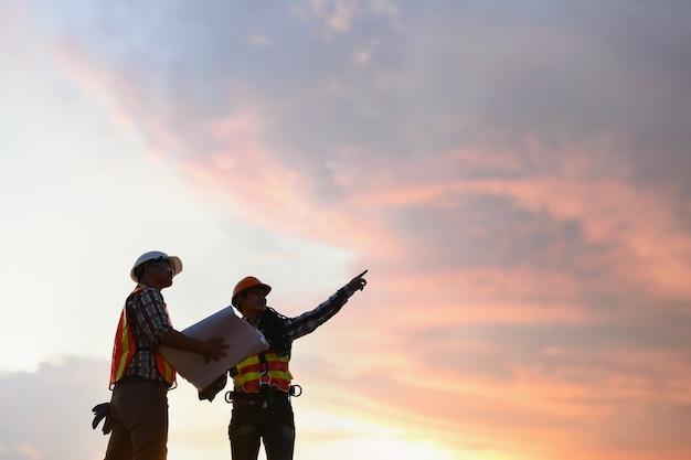 Pessoas de consultoria de engenharia no canteiro de obras, segurando a planta na mão. inspetor de construção.
