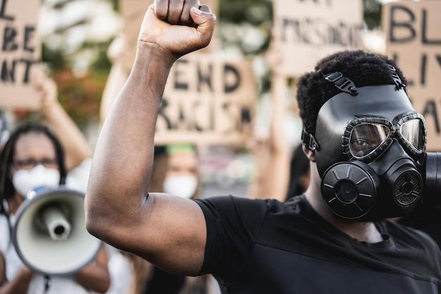 Pessoas de diferentes culturas e raças protestam nas ruas por direitos iguais - foco no homem com máscara facial