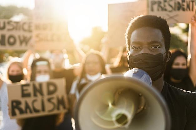 Pessoas de diferentes culturas e raças protestam nas ruas por direitos iguais - manifestantes usando máscaras durante campanha de luta contra vidas negras - foco nos olhos do homem negro
