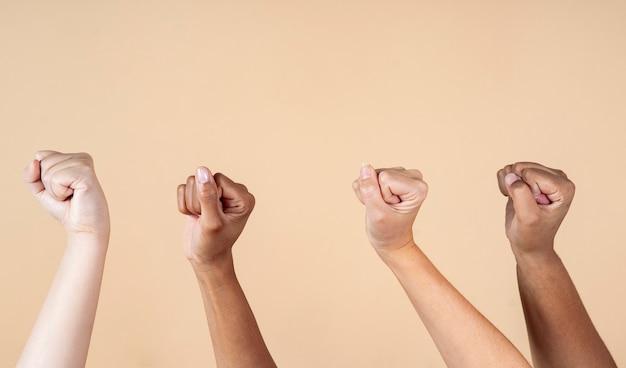 Pessoas de diferentes nacionalidades e raças levantam os punhos