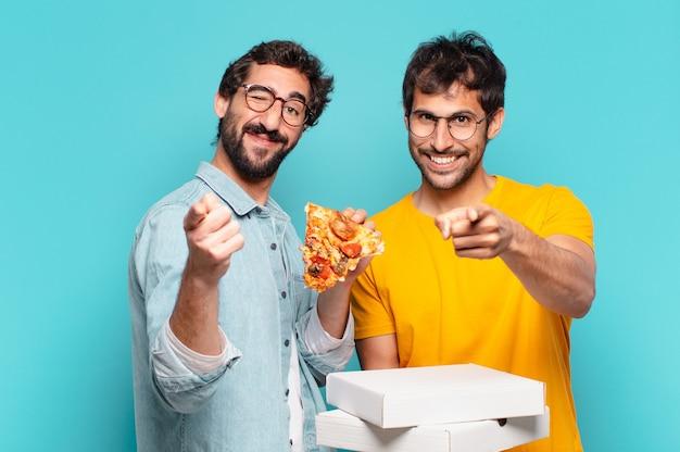 Pessoas de dois amigos hispânicos apontando ou mostrando e segurando pizzas para levar