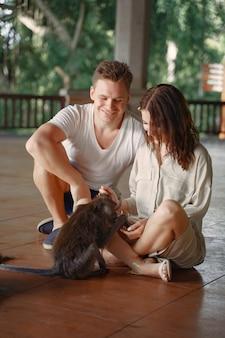 Pessoas de férias brincando com um macaco