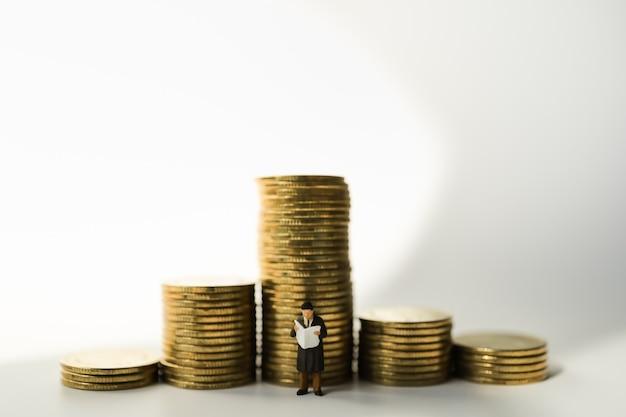Pessoas de figura em miniatura do empresário figuram em pé e lendo jornal com uma pilha de moedas de ouro.