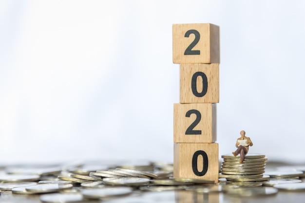 Pessoas de figura em miniatura do empresário sentado e lendo jornal na pilha de moedas com uma pilha de brinquedo de bloco de número de 2020.