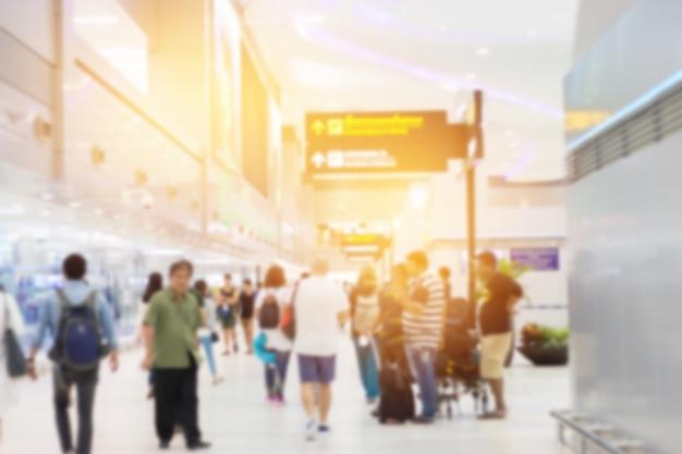 Pessoas de grande grupo que chegam e viajam transportam bagagem caminhando no prédio do terminal do aeroporto aguardando