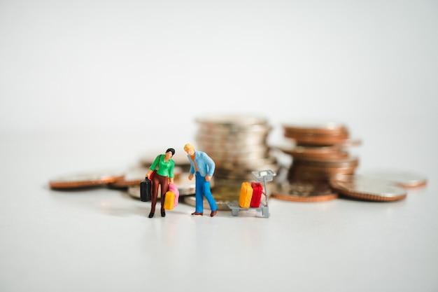 Pessoas de miniatura, homem e mulher carregam sacos no fundo de moedas de pilha