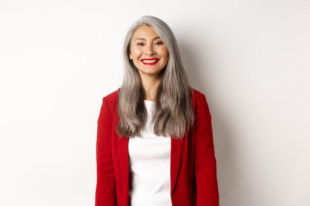 Pessoas de negócio. mulher asiática sorridente sênior com batom vermelho e blazer parecendo feliz, em pé sobre um fundo branco