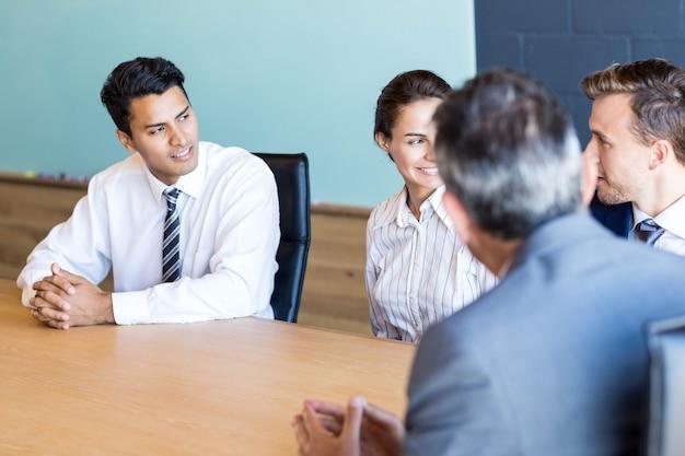 Pessoas de negócios a discutir em reunião na mesa de conferência no escritório