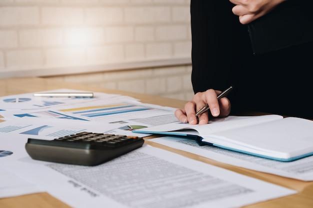 Pessoas de negócios, analisando os documentos de negócios de estatísticas, conceito financeiro