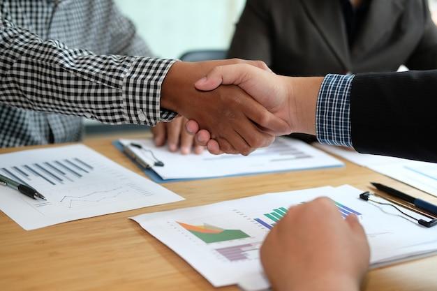 Pessoas de negócios, apertando as mãos após a reunião.