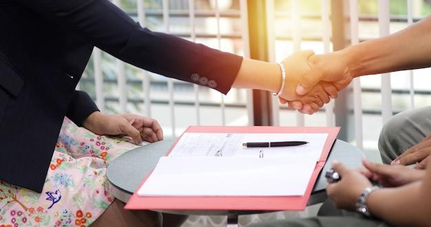 Pessoas de negócios, apertando as mãos e sorrindo seu acordo para assinar contrato e terminar uma reunião