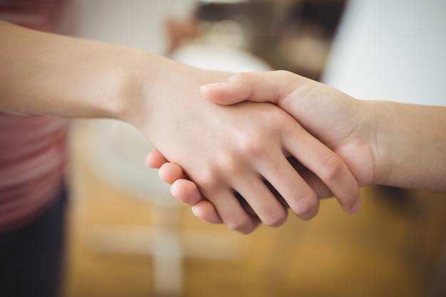 Pessoas de negócios, apertando as mãos no escritório criativo
