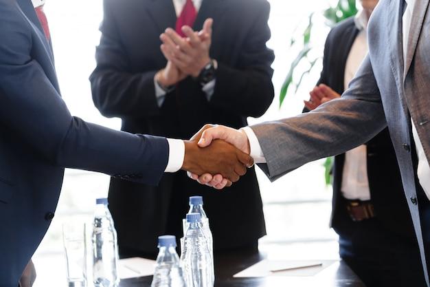 Pessoas de negócios, apertando as mãos, terminando a reunião