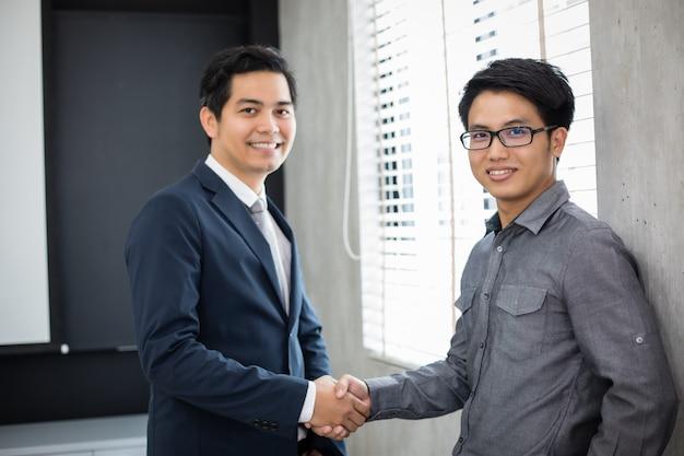 Pessoas de negócios asiáticos, apertando as mãos e sorrindo seu acordo para assinar contrato e terminar uma reunião