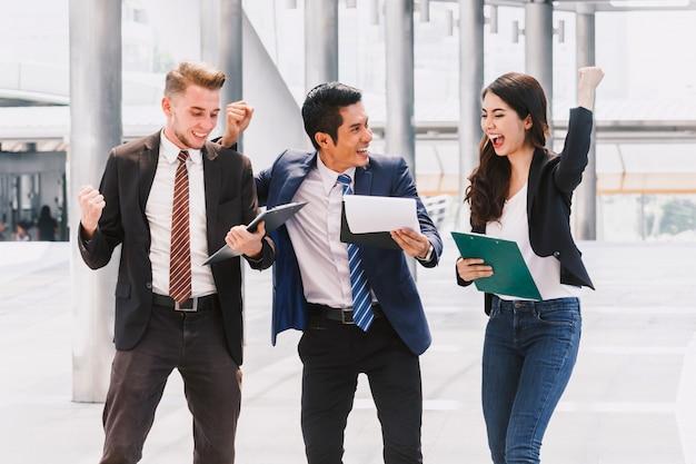 Pessoas de negócios bem sucedidos comemorando com os braços para cima